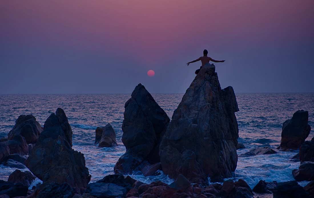 Yogi on the rock at Arambol Beach, Goa